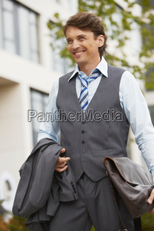 business man smiling jacket in hand