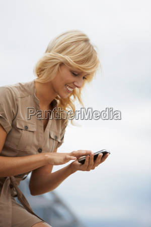 blonde woman typing in mobile phone