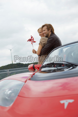 couple close together near electric car
