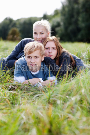 three young persons laying in grass