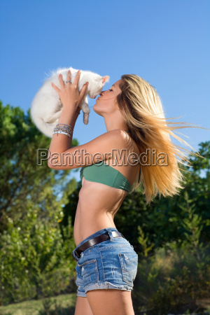 young woman kiss kitten in air
