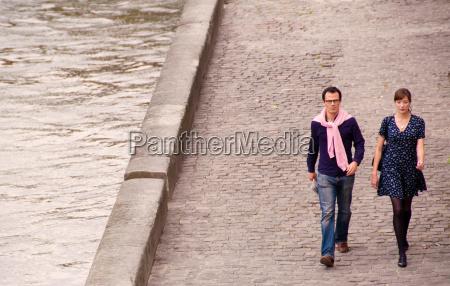 couple walk beside the seine paris