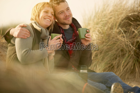 couple on beach having coffee from