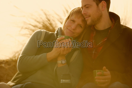 couple outdoors cuddling with coffee