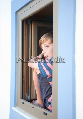 boy looking out of window at