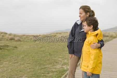 mother hugging son on beach boardwalk