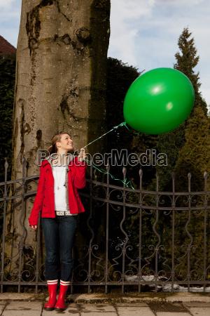 woman holding green balloon