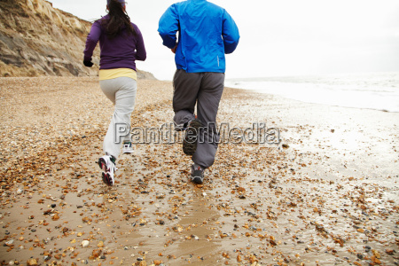 young couple running by the sea