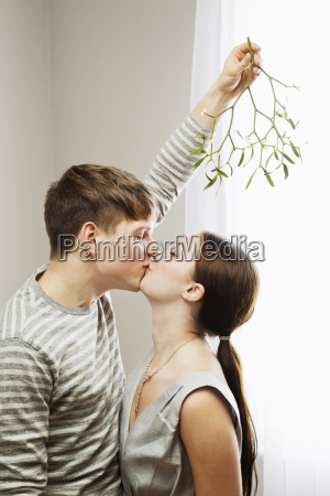 man kissing woman while holding mistletoe