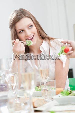 young girl eating salad at lunch