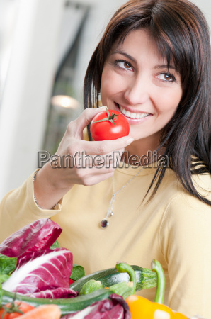 smiling woman with tomato and vegetables