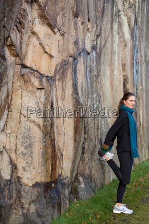 woman stretching in front of rock