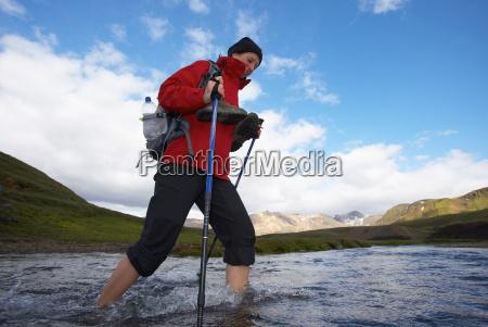 woman traversing shallow river