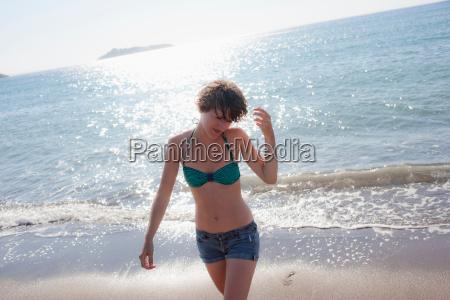 woman in bikini walking on beach