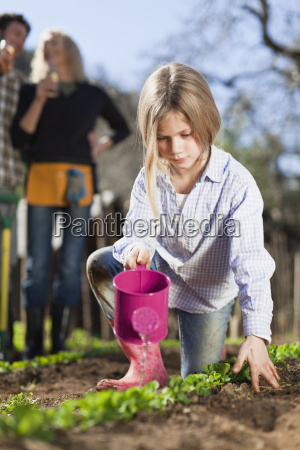 girl watering plants in garden