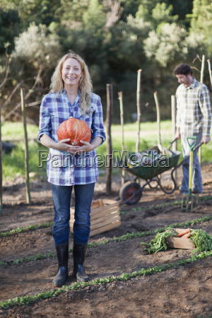 woman carrying gourd in garden