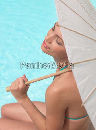 woman sitting by pool under umbrella