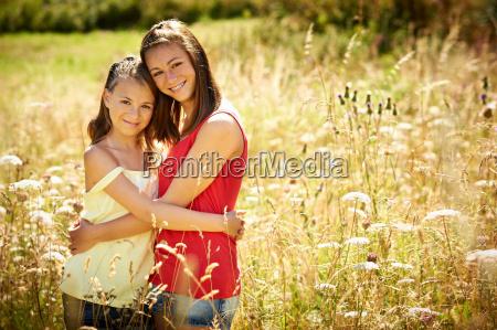 girls hugging in tall grass