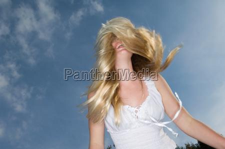 teenage girl tossing her hair outdoors