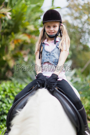 smiling girl riding horse in park