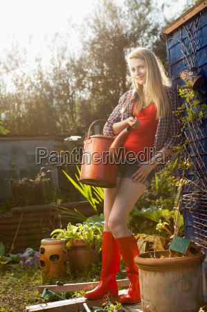 woman holding watering can in garden