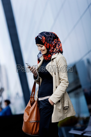 woman, in, headscarf, using, cell, phone - 18284070