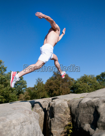 rock climber jumping between rocks