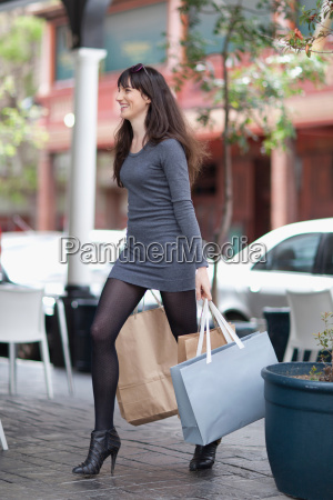 woman carrying shopping bags in city