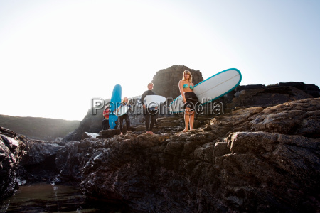 four people carrying surfboards