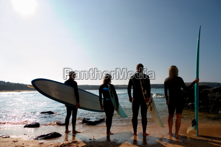 four people holding surfboards