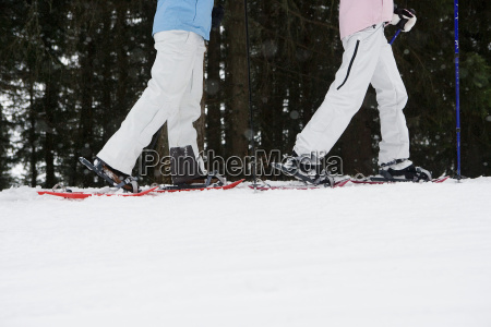 two women walking in snow shoes