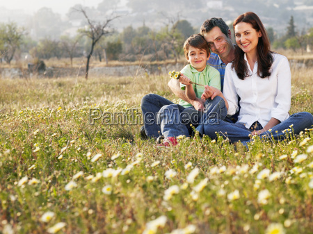 parents and son sitting in field