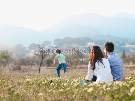 parents sitting in field watching son