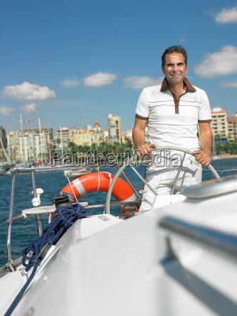 mature man steering yacht smiling