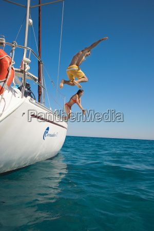 young couple jumping off yacht into
