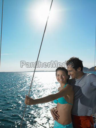 young couple standing on yacht at