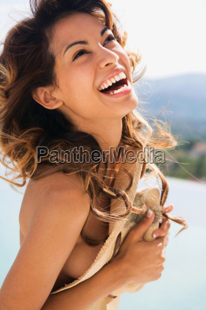 woman laughing and holding a hat