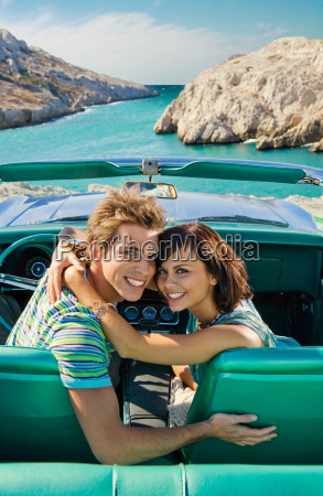 man and woman in car smiling