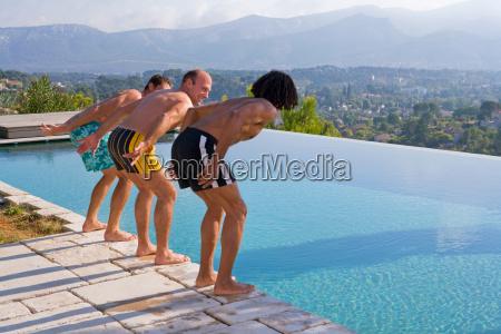 men diving into a pool