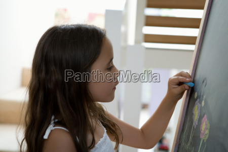 young girl writing on a chalk