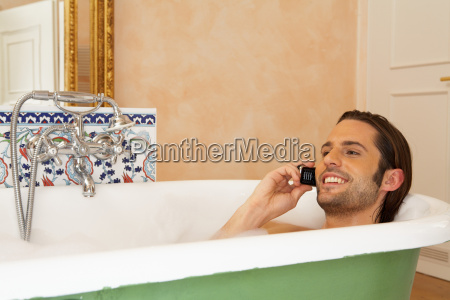 young man smiling in bath holding