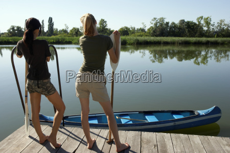 two young women standing on pier