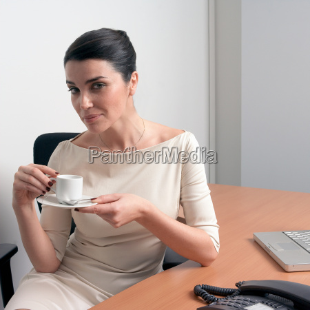 woman in office holding cup