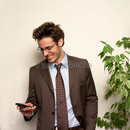 man holding phone in office smiling