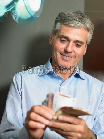 mature man counting banknotes smiling