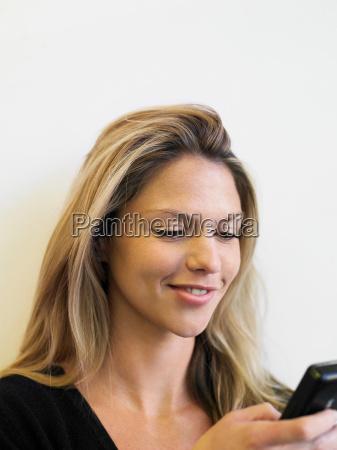 young woman using palmtop smiling