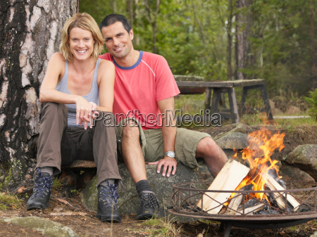 couple sitting by a fire pit
