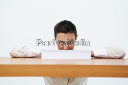 portrait of woman looking over paper