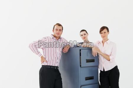 three business people lean on cabinet
