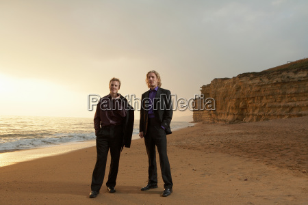 two men standing on beach at